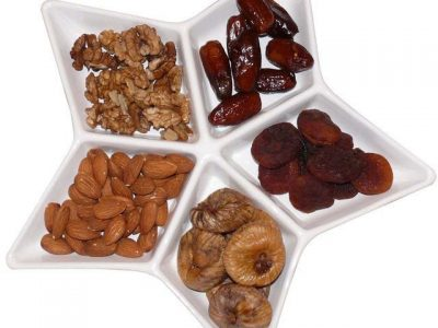 A star plate with different kinds of foods in the different sections. The foods are walnuts, dates, dried apricots, dried figs, and almonds